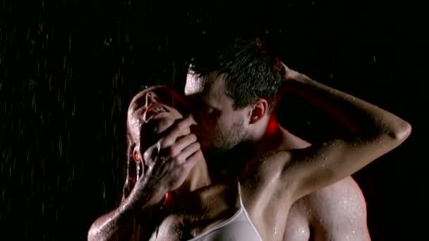 Leidenschaftliche Liebhaber küssen unter Regen halbnackt, Frau genießen warme nasse Küsse im Hals von heißen Kerl.