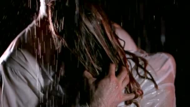 Nahaufnahme eines Kerls umarmt sein Mädchen eng unter Regen, halten enge Frauen nassen Körper.