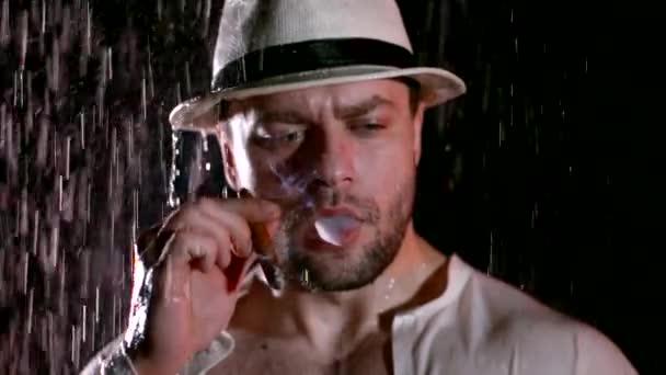Porträt eines Gangsters mit Zigarre im Regen. sexy gutaussehender Kerl in weißem Hemd und Hut, Zigarre rauchend, isoliert auf schwarzem, brutalem Gangsterkonzept.