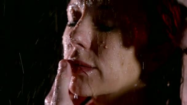 Detailní záběr záběr obrátil na ženy, za deště, muž běží svůj prst na její vlhké rty, vášeň a lásku.