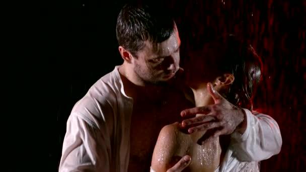 Muž objímá jeho krásná žena v dešti, mokré pár izolovaných na černé.