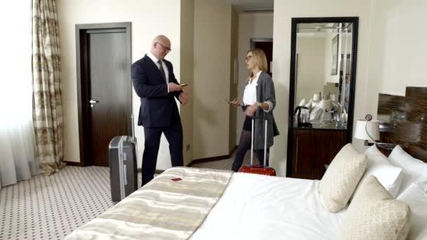 Geschäftspartner im Urlaub auf einer Reise, glücklich, am Zielort im Hotelzimmer anzukommen. Glatzkopf in Brille und Businessanzug zeigt Daten auf dem Smartphone-Bildschirm