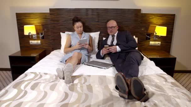 Pár dospělých podnikání pomocí smartphone a tablet počítač v ložnici během vašeho pobytu v hotelu