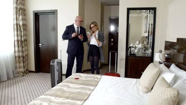 dva podnikatelé-muže a ženy v podnikání vyhovuje kontrola do hotelového pokoje, služební cesty