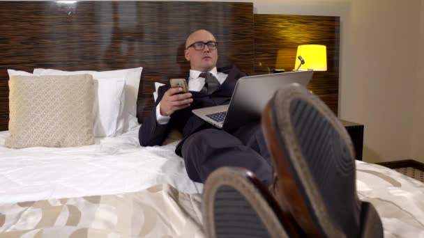 tired businessman is relaxing in bedroom of hotel in evening, he is wearing suit, typing on phone