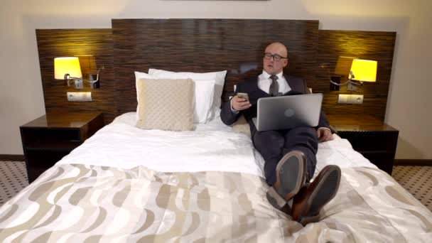 man is relaxing in hotel room during business trip, lying in bed dressed in suit, holding laptop