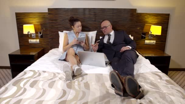 adult businessman and his wife are lying in bed in hotel room, using gadgets and chatting