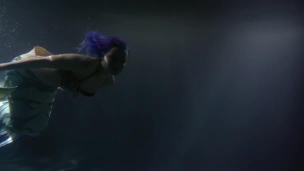 mladá půvabná mořská panna s modrými vlasy se topí v oceánu vody v noční době, kymácející ocas