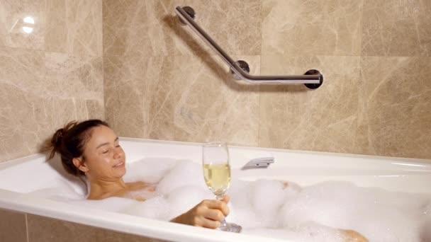 Happy nahá žena je relaxační koupel s pěnou v regionu champagne domů, pití, usměvavý, zvedání nohou