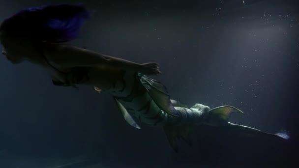 magické štíhlá a krásná žena mořská panna se topí v hloubku oceánu, mává ocasem dlouhým