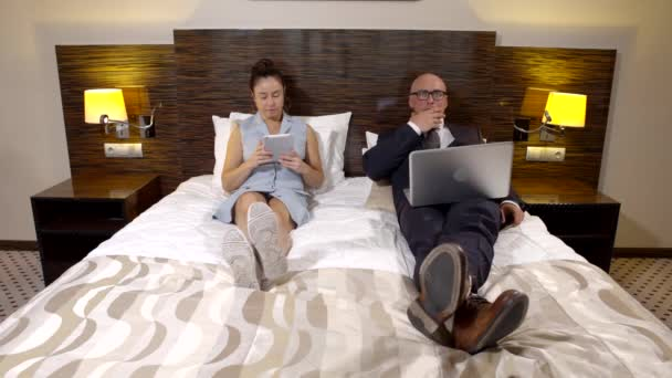 Business partners lie in a hotel room on a bed in shoes. a bald man in glasses and a suit working on a laptop and a dark-haired woman looking at a tablet.