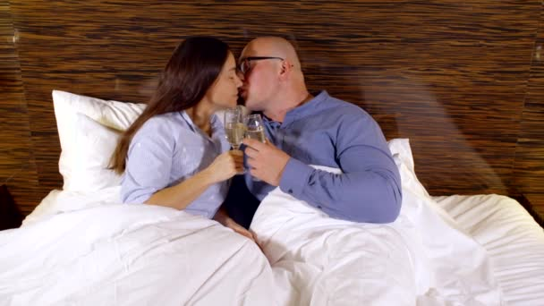 Dunkelhaarige Frau und kahlen Mann mit Brille im Bett liegend, klar Trinkgläser Glas Champagner, küssen, Lächeln.