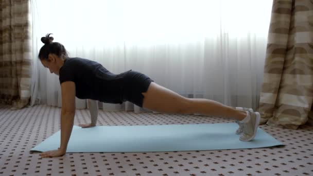 Sporty woman doing regular pushups in a living room, home workout session.