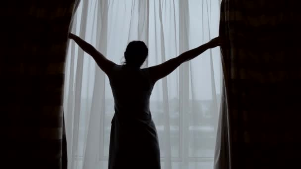Shot from behind of a woman opening curtains after waking up in a morning, looking out of the window.