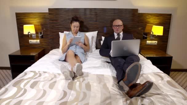 Manžel a manželka leží v posteli s miniaplikacemi, nemluvit. Lidé ve formální oděv s notebookem a manželka, pomocí tabletu pro konverzaci na internetu.