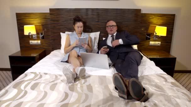 Geschäft und seine Frau liegen im Bett eines Hotelzimmers mit Gadgets.
