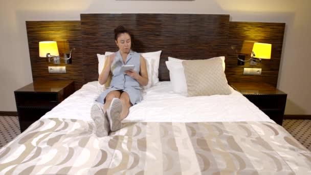 Příležitostné bruneta žena leží v posteli hotelového pokoje v šatech a bílé boty surfování webu na tabletu.