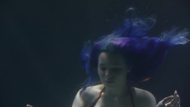 Beautiful underwater close-up of a young princess of underwater world, charming mermaid with purple hair.
