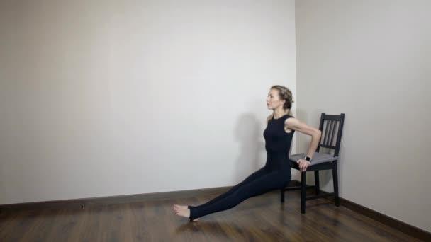 instruktor pro obnovu pohybového systému těla ukazuje trénink svalů rukou triceps doma s pomocí židle