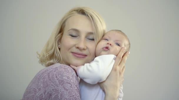 mladá blondýna matka s krátkými vlasy, usmíval se, držela baculaté miminko v náručí, stiskne jí, Polibky.