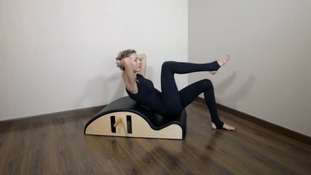 Sporty woman morning Pilates workout in home interior. Young woman doing gym workout at home. Healthy and sporty lifestyle