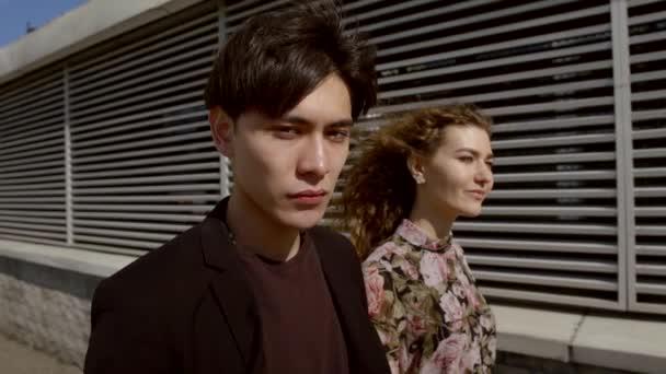 Zeitlupe. internationales Paar geht am Nachmittag bei windigem Wetter auf die moderne Stadt. piercing aussehen der asiatische Männer in die Kamera