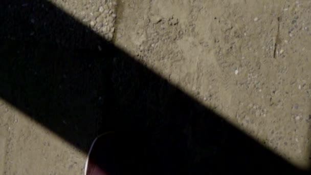 Mann in Jeans und Turnschuhen läuft draußen auf Asphalt und filmt seine Füße