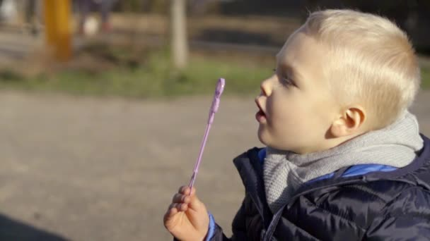 Close-up shot of a adorable blonde little boy blowing soap bubbles, fun outdoor activities.