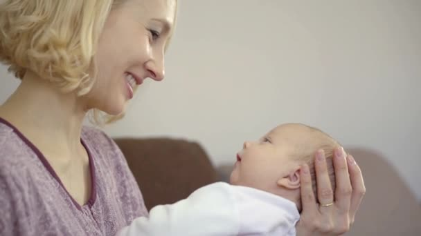 Side view shot of a beautiful blonde mother cuddling and playing with her infant baby.