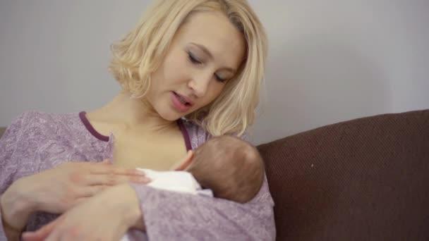 Loving mother breasfeeding her baby indoor.