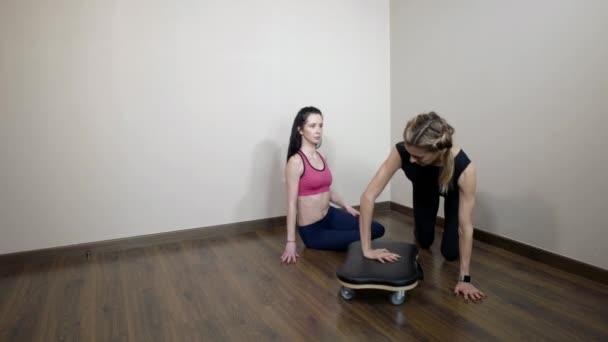 személyi edző nő mutatja a fizikai testmozgás a fiatal barna fitness terem, a görgős állvány