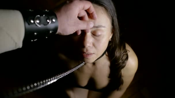 adult female slave is standing on knees in front of man, he is filming her and touching face by hand