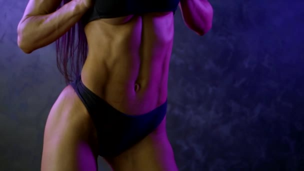 sexy bodybuilder woman is showing her slim and strong body in bikini, moving hips in studio