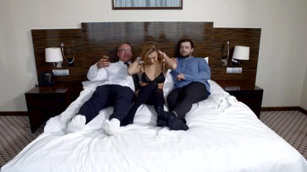 Schlankes Mädchen in Unterwäsche liegt mit zwei Männern im Bett. alte Freunde ruhen sich im Hotel aus und werden mit dem Handy fotografiert