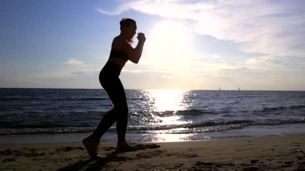 Sporty woman doing combat yoga. Beautiful summer sunset at the seaside. Silhouette of woman practicing physical activity the Concept of active healthy way of life.