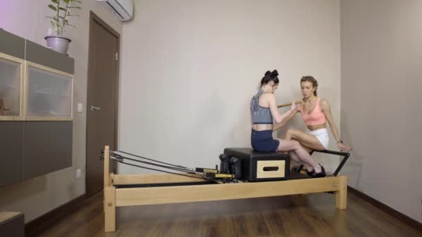 Pilates instructor trains a young slender girl. woman workout gym exercise in home interior. Gymnastics and fitness concept for women