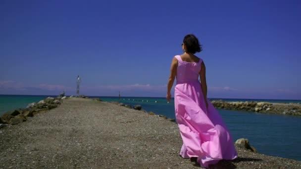Egy gyönyörű nő egy rózsaszín ruhában sétál át a tengeren kavicsos strand és reméli, elgondolkodva