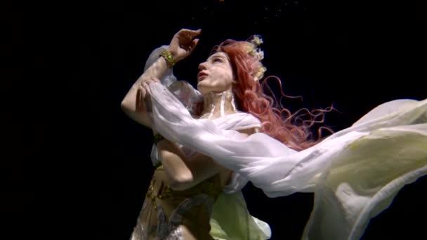 krásná víla s růžovými vlasy plaví pod vodou na černém pozadí jako pohádkový hrdina