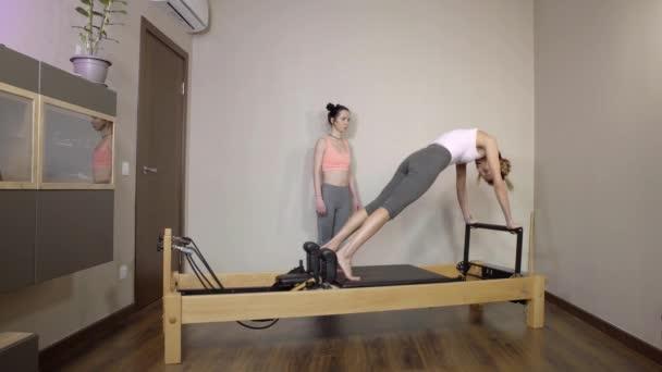 Fitness, stretching gyakorlat, egy csoport két vonzó boldog mosolygó fiatal nők dolgoznak otthon a Pilates szimulátor csinál multi-funkcionális képzés