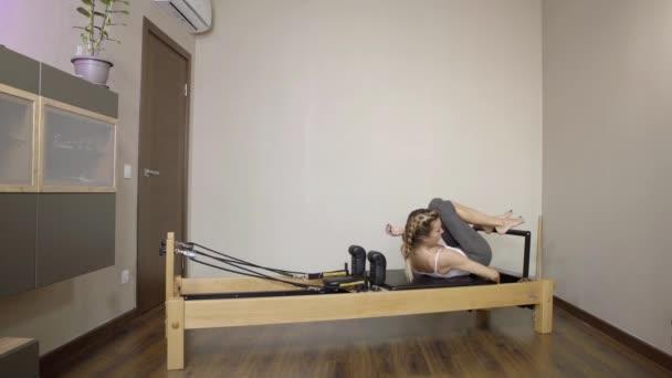 Pilates. Nő a Sportruházat gyakorló nyújtó gyakorlatokat a reformátor edzőteremben