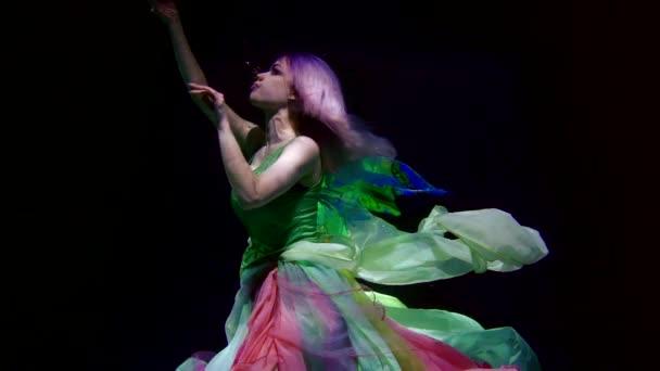 Krásná žena v jasných šatech a modrých vlasech pod vodou jako mořská panna ve tmě