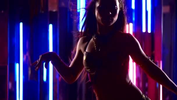 schöne junge sexy Mädchen in orientalischen Kleidern tanzen in Neonlicht