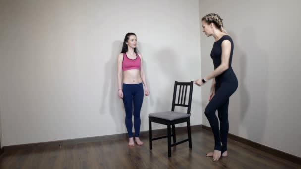 der Körperhaltungslehrer schult ein junges schlankes Mädchen zu Hause so schnell wie möglich, um die Beweglichkeit des Körpers nach einem langen Arbeitstag wiederherzustellen
