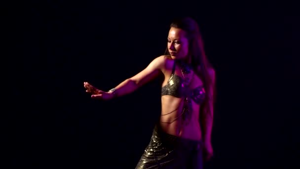 Slender woman dancing belly dance in a dark Studio. Black background. Slow motion