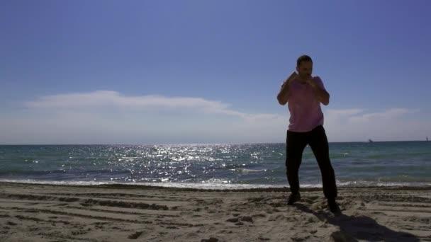 Silueta muže, který se zabýval bitvou se stínem na pláži večer. Trénink boxování