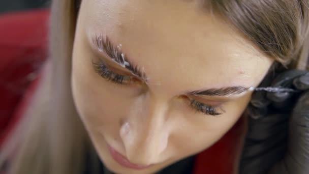 Professional beautician performing eyebrow treatment at spa salon.
