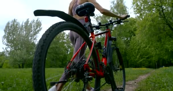 Sporty woman riding a bike in the background of the summer Park. The girl rolls her bike. sport women lifestyle