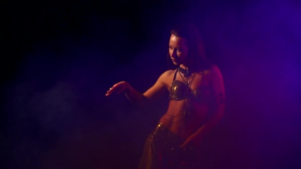 verführerische sexy traditionelle orientalische Bauchtanzmädchen, die vor dem Hintergrund von ungleichmäßigem Licht im Rauch tanzen. eine Frau in einem exotischen Kostüm bewegt ihren halbnackten Körper sexuell