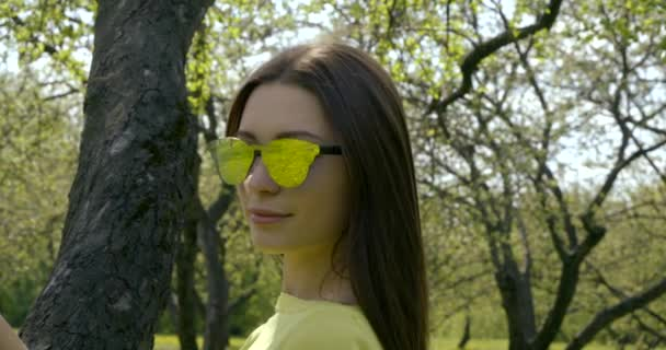 Portrait of attractive woman in mirrored sunglasses smiling while standing in city Park on summer day. The concept of people and sunlight