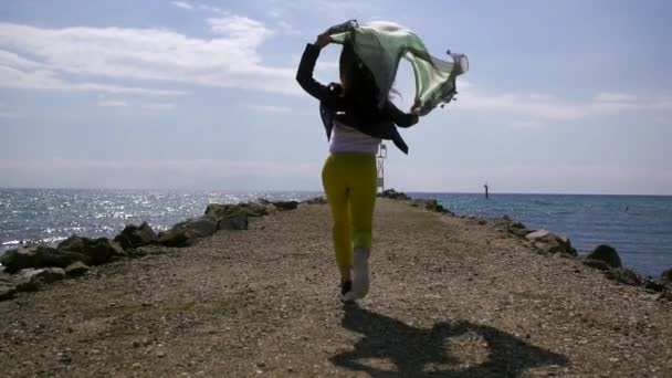 carefree woman is running over breakwater on sea shore, waving by fabric over head in sunny weather
